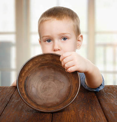 Cute blonde boy shows empty plate